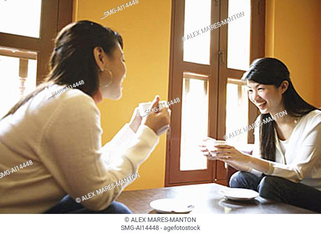 Two young women, sitting face to face, holding cups of coffee