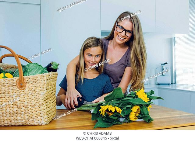 Mother and daughter in kitchen cutting sunflowers