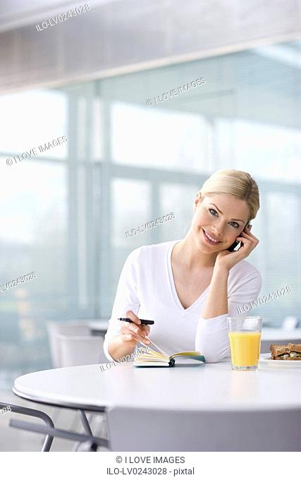 A woman in a cafe or office canteen, talking on a mobile phone whilst checking her diary