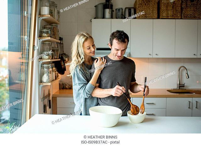 Mid adult couple mixing salad bowl in kitchen