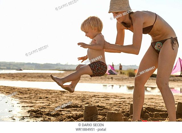 Croatia, Dalmatia, Mother And Son On Sandy Beach
