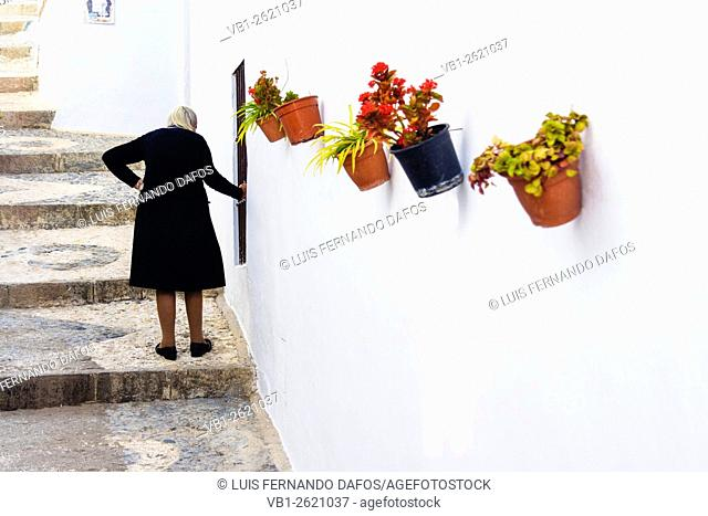 Old Spanish widow dressed in black on her way up the cobbled paved stairs of a whiwashed lane decorated with colorful pots in Frigiliana, Malaga, Andalusia