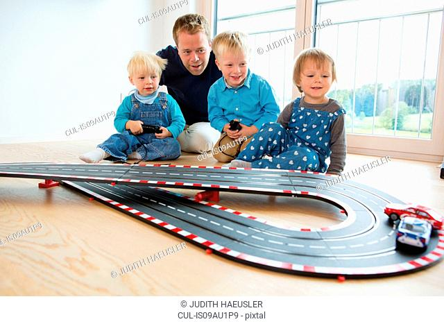 Mid adult man and three young children playing with toy racing cars on living room floor