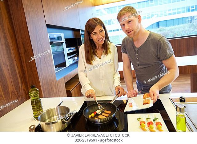 Family in the kitchen. Couple. Healthy eating. Healthy growth. Cooking fish and vegetable skewer