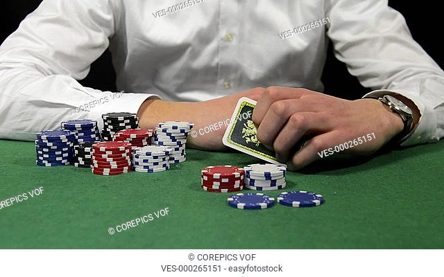 Poker player with a stack of chips showing his hand with a pair of kings, sitting back and folding his arms