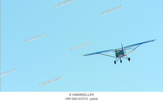 TS WS Light aircraft flying in air and turning to its left / Howick, KwaZulu-Natal Province, South Africa