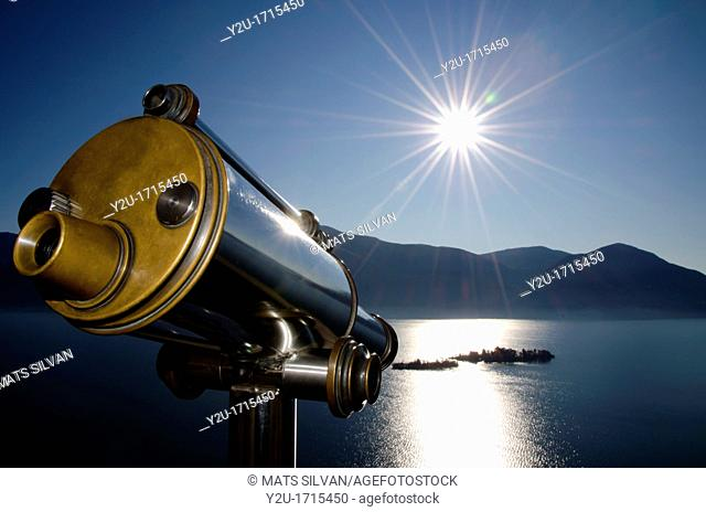 Watching with a telescope brissago islands on an alpine lake maggiore with mountains and sunbeam in switzerland