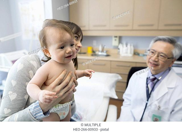 Pediatrician talking to mother with baby examination room