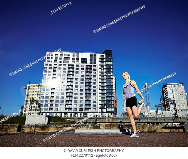 Female runner stretching before a run in an urban environment; Montreal, Quebec, Canada