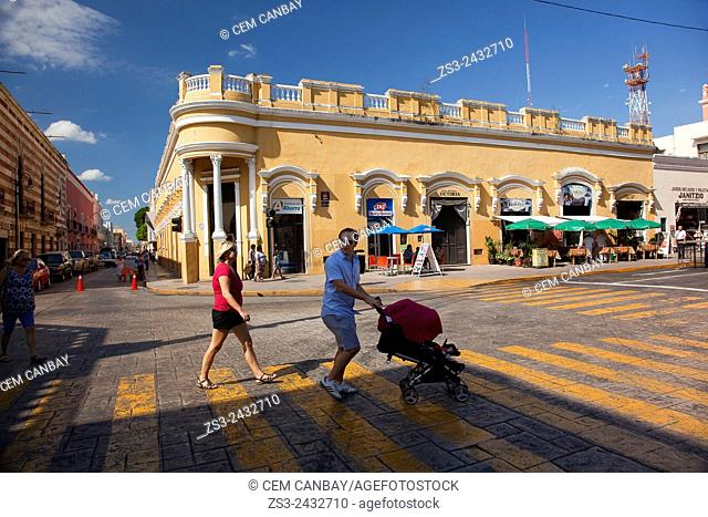 People at the pedestrian crossing near the Palacio Municipal and Ayuntamiento-Town Hall in Zocalo at the historic center, Merida, Yucatan Province, Mexico