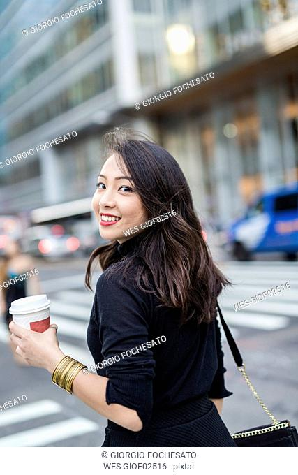 USA, New York City, Manhattan, portrait of smiling young woman with coffee to go crossing the street