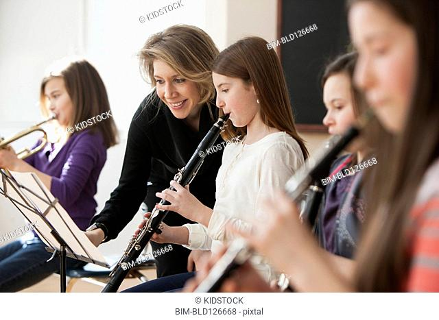 Caucasian teacher helping students in music class