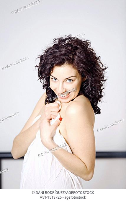 Portrait of a beaitiful woman covering her body with sheets and smiling at camera