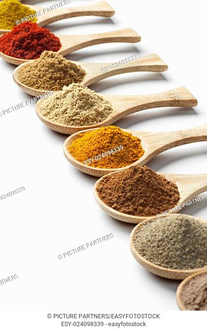 Variety of dried herbs and spices on wooden spoons