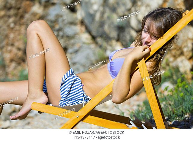 Lying on a chair on the beach young woman