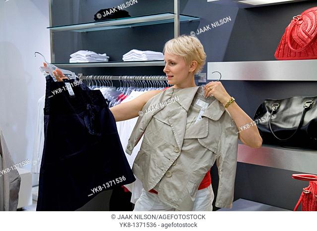 Young woman shopping and comparing different clothes in store