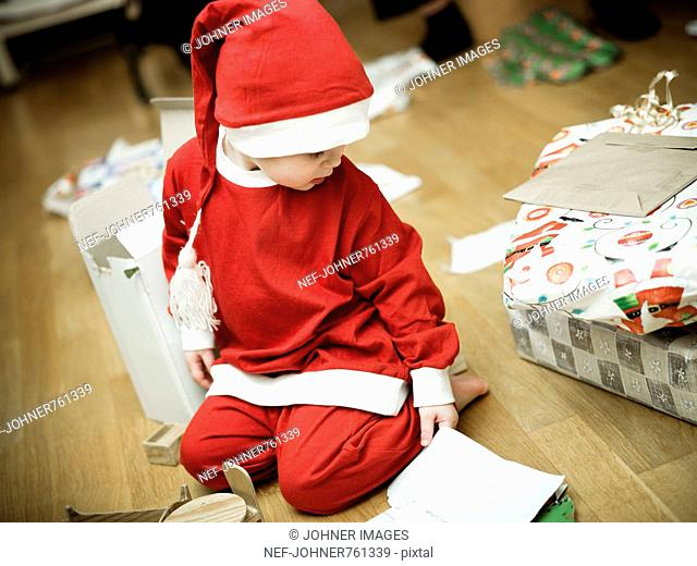 Girl dressed as Santa Claus opening Christmas presents, Sweden