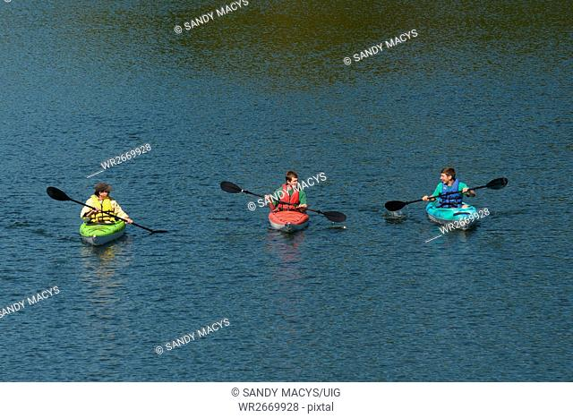 A group of kayakers paddle on the Waterbury Reservoir in Waterbury, Vermont dring the fall as colors start to turn brilliant