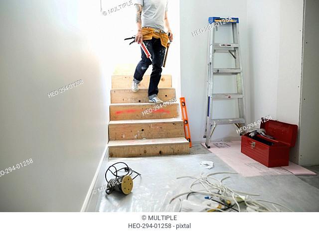Man with caulk gun descending stairs toward home improvement project