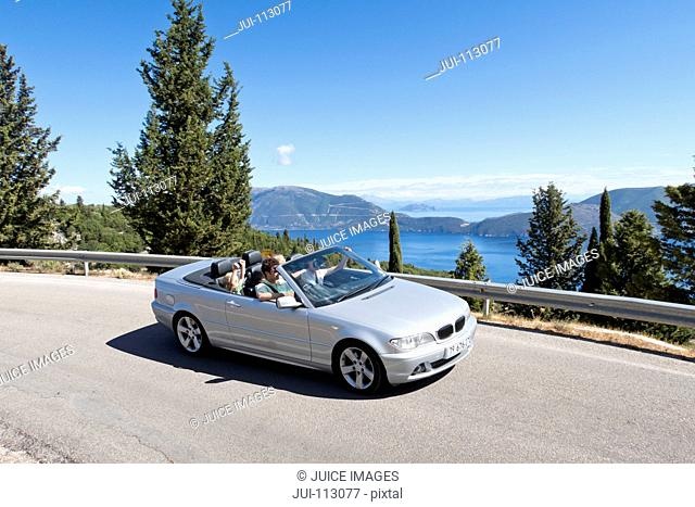 Family riding in convertible on sunny, winding road along ocean