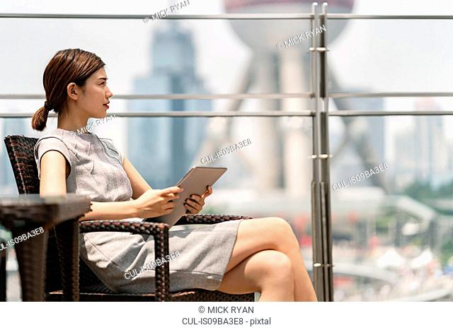 Young businesswoman with digital tablet at sidewalk cafe in Shanghai financial centre, Shanghai, China