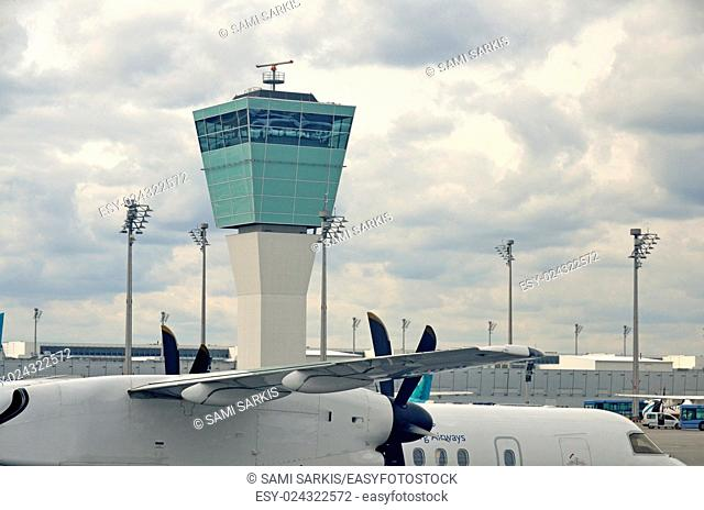 Stationary airplane on tarmac by Air Traffic Control Tower, Munich, Germany