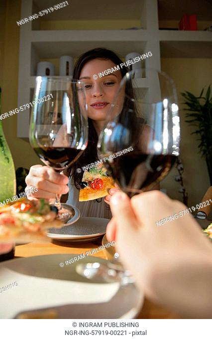 Romantic couple dating at home. Drinking red wine, eating fresh homemade pizza. Photo from the first person