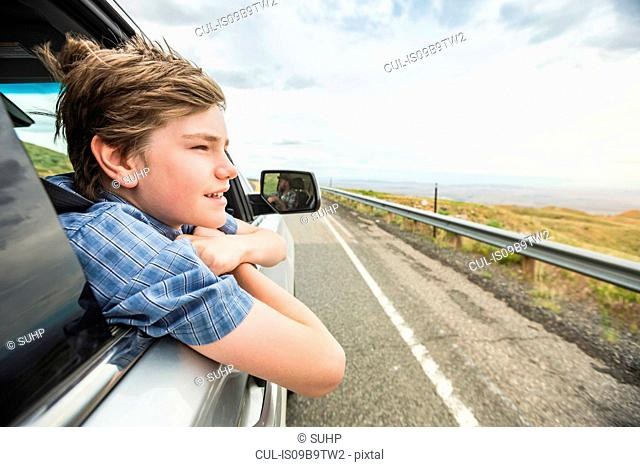 Boy on road trip leaning out of car window