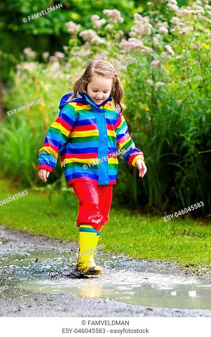 Little boy and girl play in rainy summer park. Children with colorful rainbow jacket and waterproof boots jump in puddle and mud in the rain