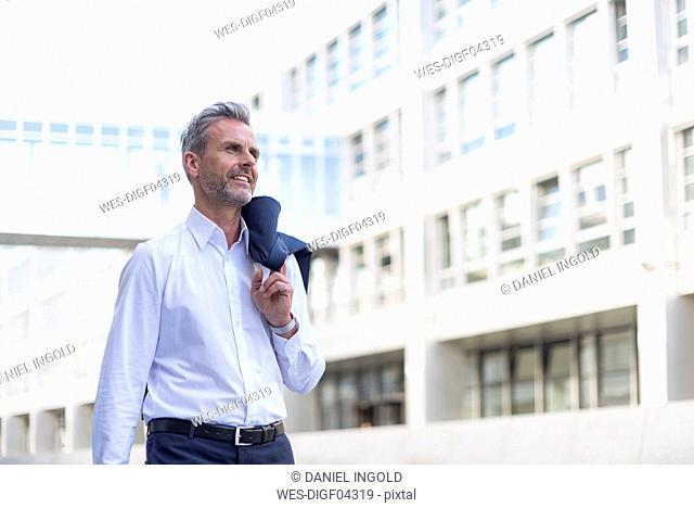 Businessman walking in front of modern office building