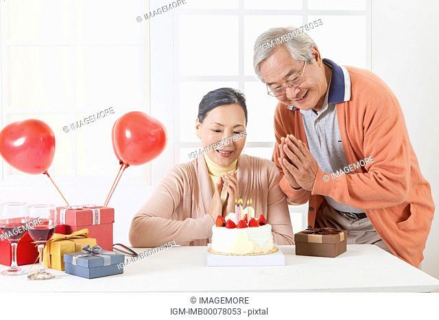 Senior couple celebrating birthday and smiling happily