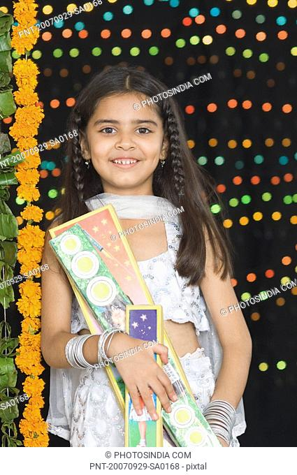 Portrait of a girl holding diwali crackers