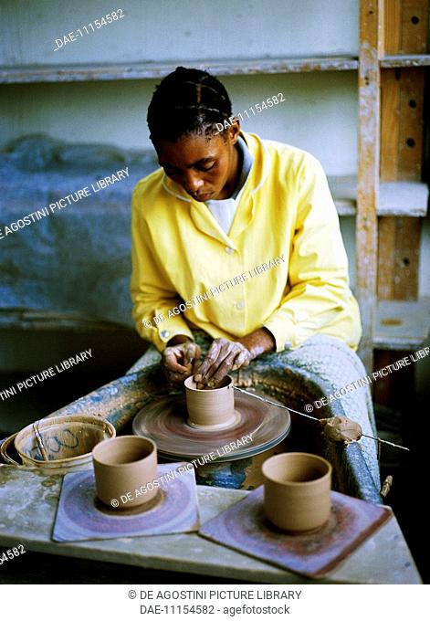 Craftsman making terracotta pottery on a potter's wheel, Lesotho