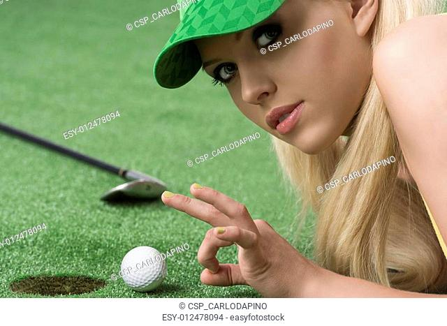 girl's playing with golf ball looks in to the lens