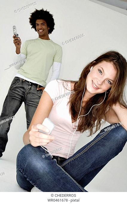 Portrait of a young woman listening to an MP3 player and a young man using a mobile phone behind her