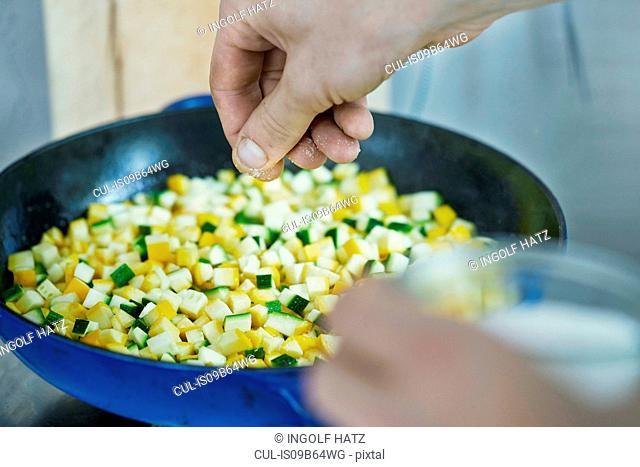 Chef seasoning vegetables in frying pan, close-up
