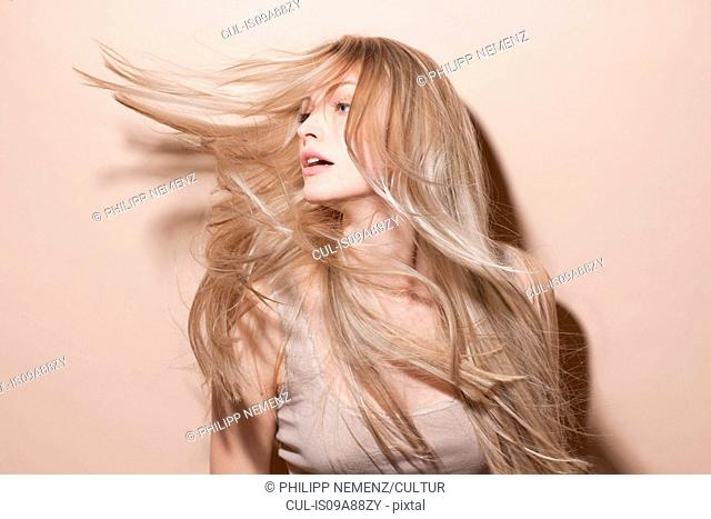 Young blonde woman flicking hair