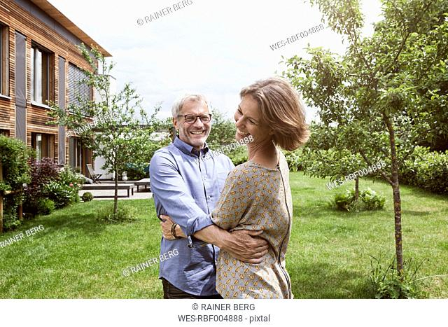 Happy mature couple dancing in garden