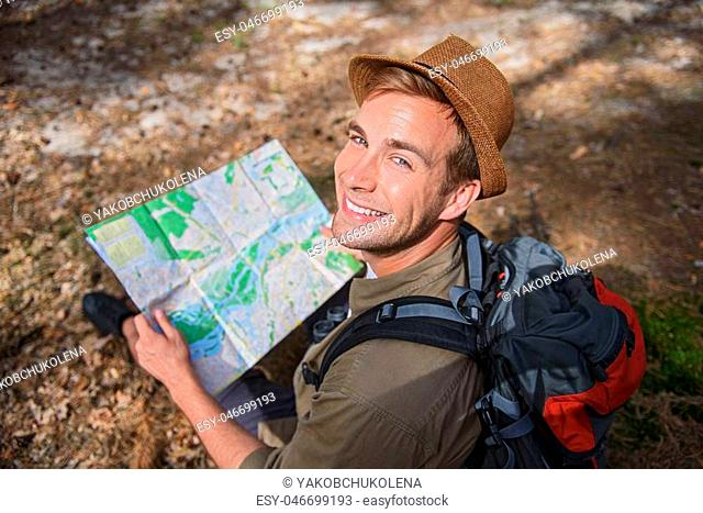 Cheerful male traveler is reading a map with joy. He is sitting and looking at camera happily. Man is smiling
