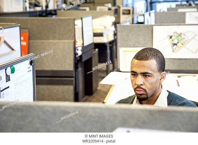 A Black man working in his cubicle in an corporate office