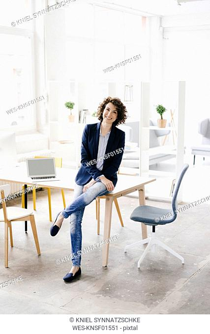 Businesswoman in office sitting on desk, looking confident