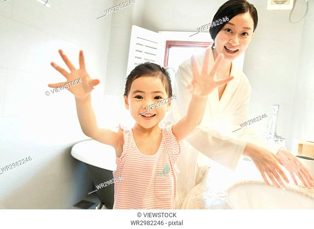 Little girl playing with mother at bathroom