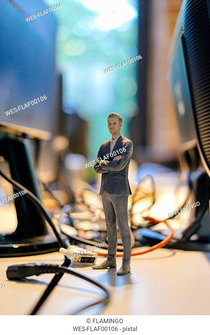 Businessman figurine standing amidst computer cables