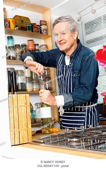Man opening bottle of wine in kitchen