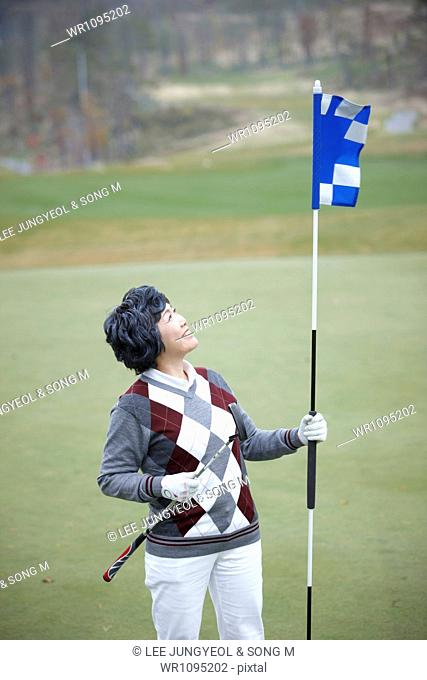middle aged woman holding a flag on golf field