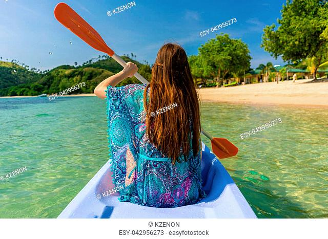 Rear view of a young woman with long brown chestnut hair paddling a canoe along the shore of an idyllic island during vacation in Indonesia