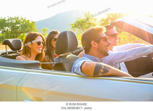 Four adult friends driving on rural road in convertible, Majorca, Spain