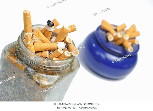 Cigarettes butts in jar and ashtray, white background