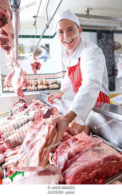 Smiling butcher arranging meat in display case