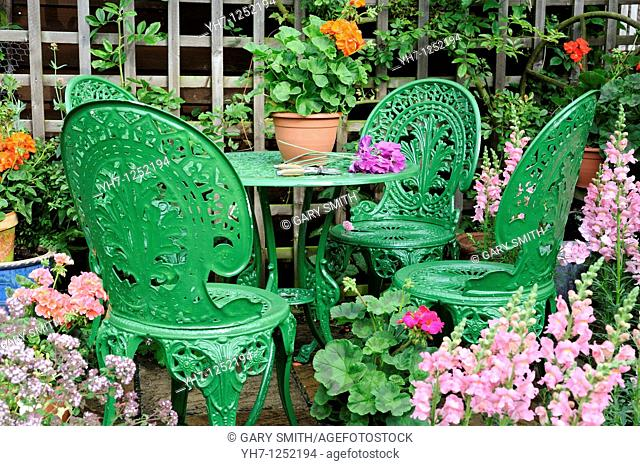 summer seating area with garden furniture, potted geraniums, antirrhinums and panama hat, norfolk, uk, july